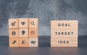 Business target concept with wooden blocks with icons on it on dark color background side view